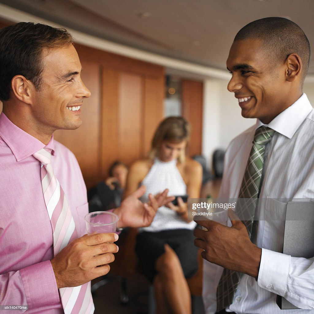 side profile of two businessmen talking at the office : Stock Photo