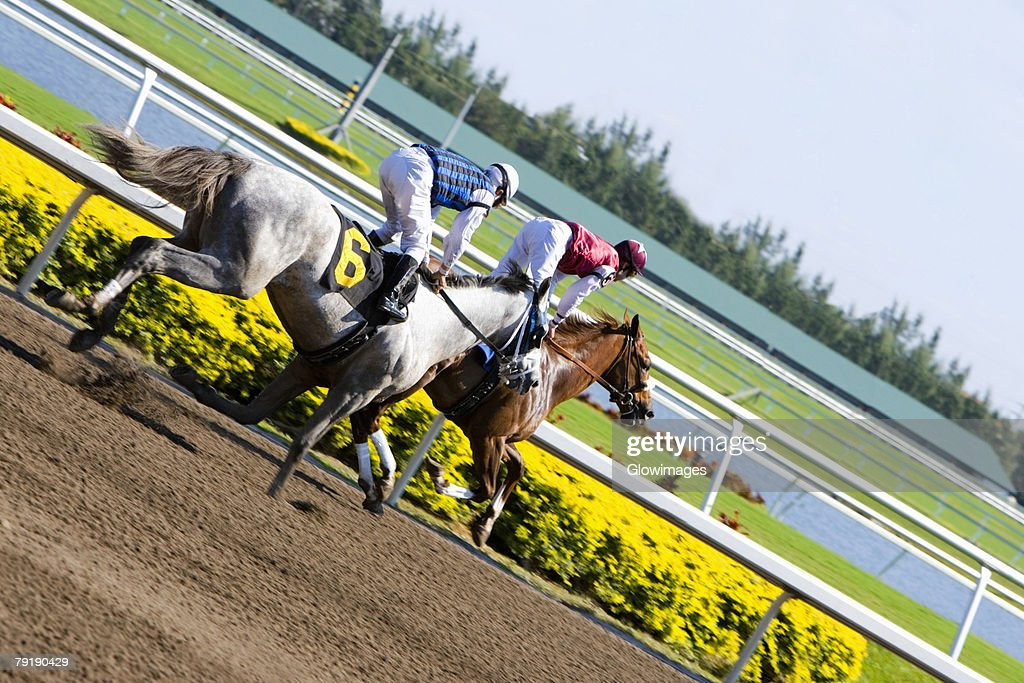 Side profile of two jockeys riding horses in a horse race : Stock Photo