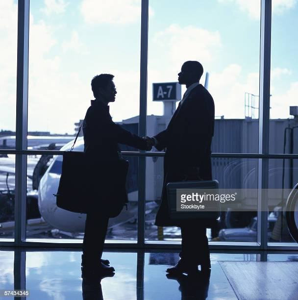 side profile of two men shaking hands at the airport