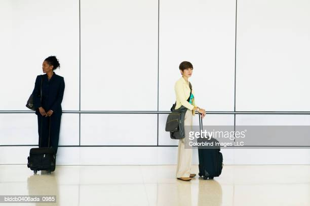 Side profile of two young businesswomen standing in an airport with luggage