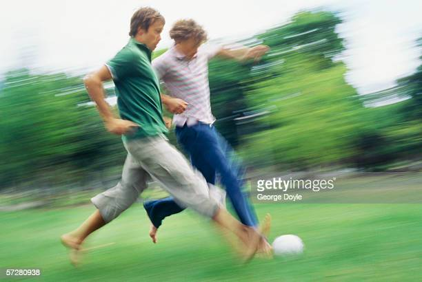Side profile of two young men playing soccer in a park