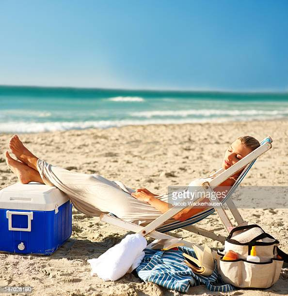 Side profile of woman sleeping on deck chair at beach