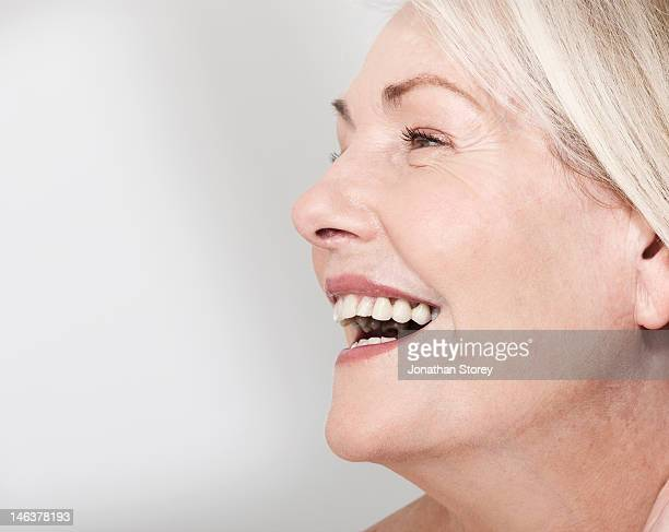 Side profile shot of mature woman's face laughing