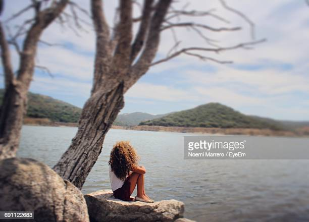 Side View Full Length Of Woman Sitting On Rock Against Lake