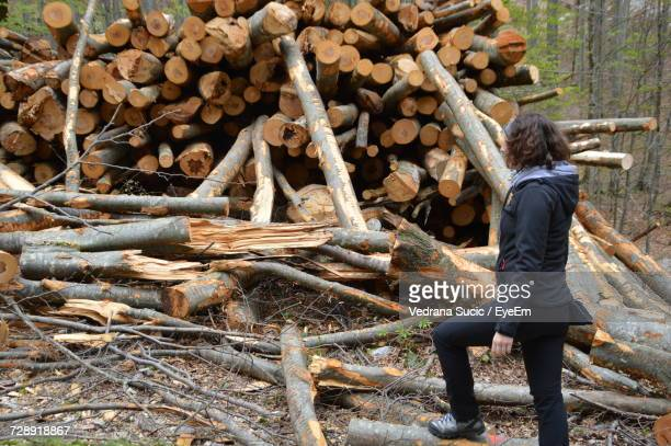 Side View Full Length Of Woman Standing By Logs At Forest