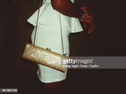 Side view mid section of woman in white dress carrying sling bag