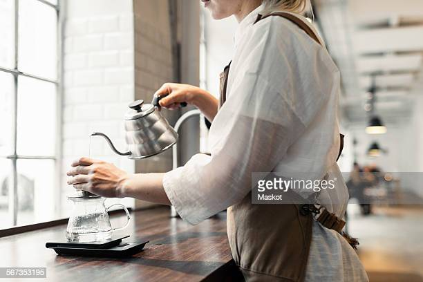 Side view midsection of female barista pouring boiling water in coffee filter at cafe counter
