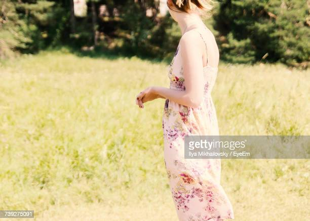 Side View Midsection Of Woman Standing On Grassy Field