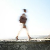 Side View Of A Blurred Woman Walking Against Sky