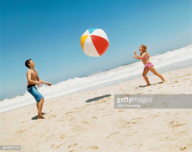 Side View of a Brother and Sister Playing With a Beach Ball