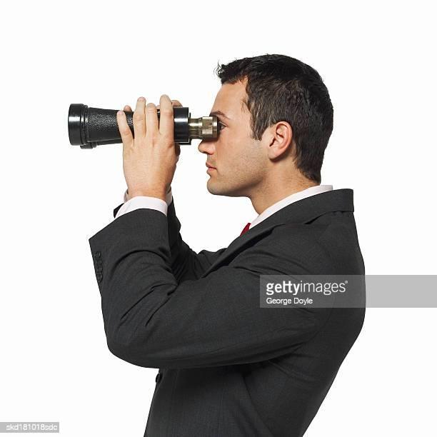 side view of a businessman looking through binoculars