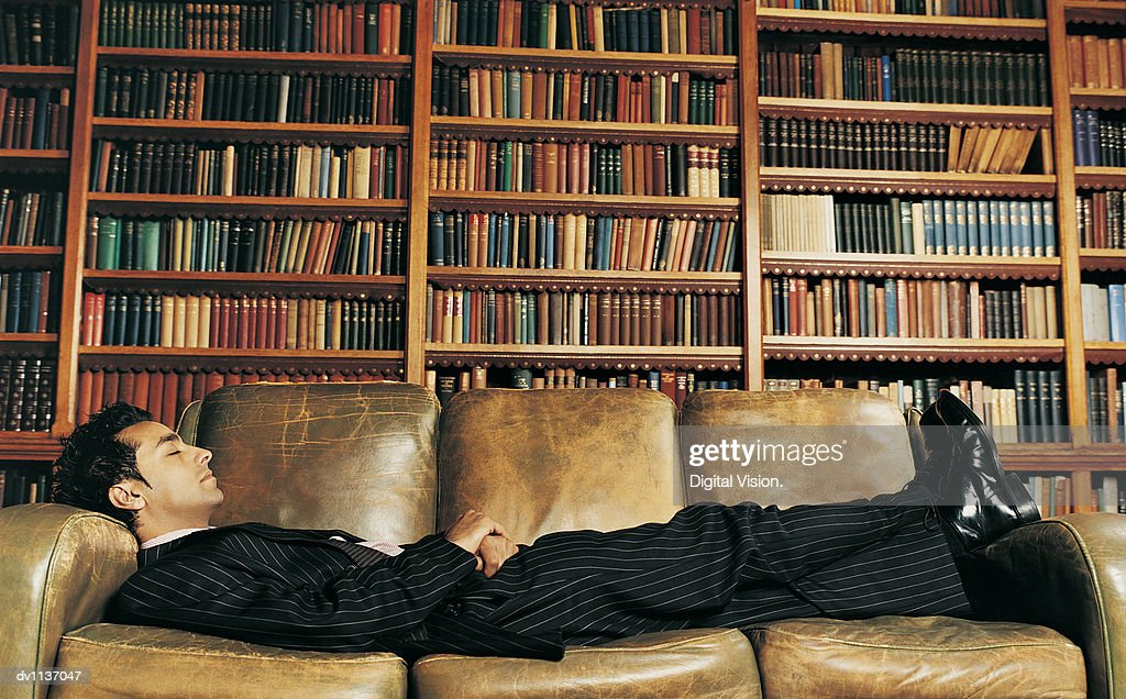 Side View of a Businessman Lying Asleep on a Leather Sofa in Front of a Large Group of Books on Shelves : Stock Photo