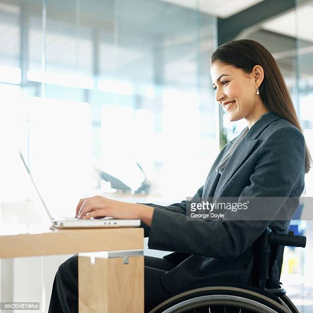 side view of a businesswoman sitting in a wheelchair working on her laptop