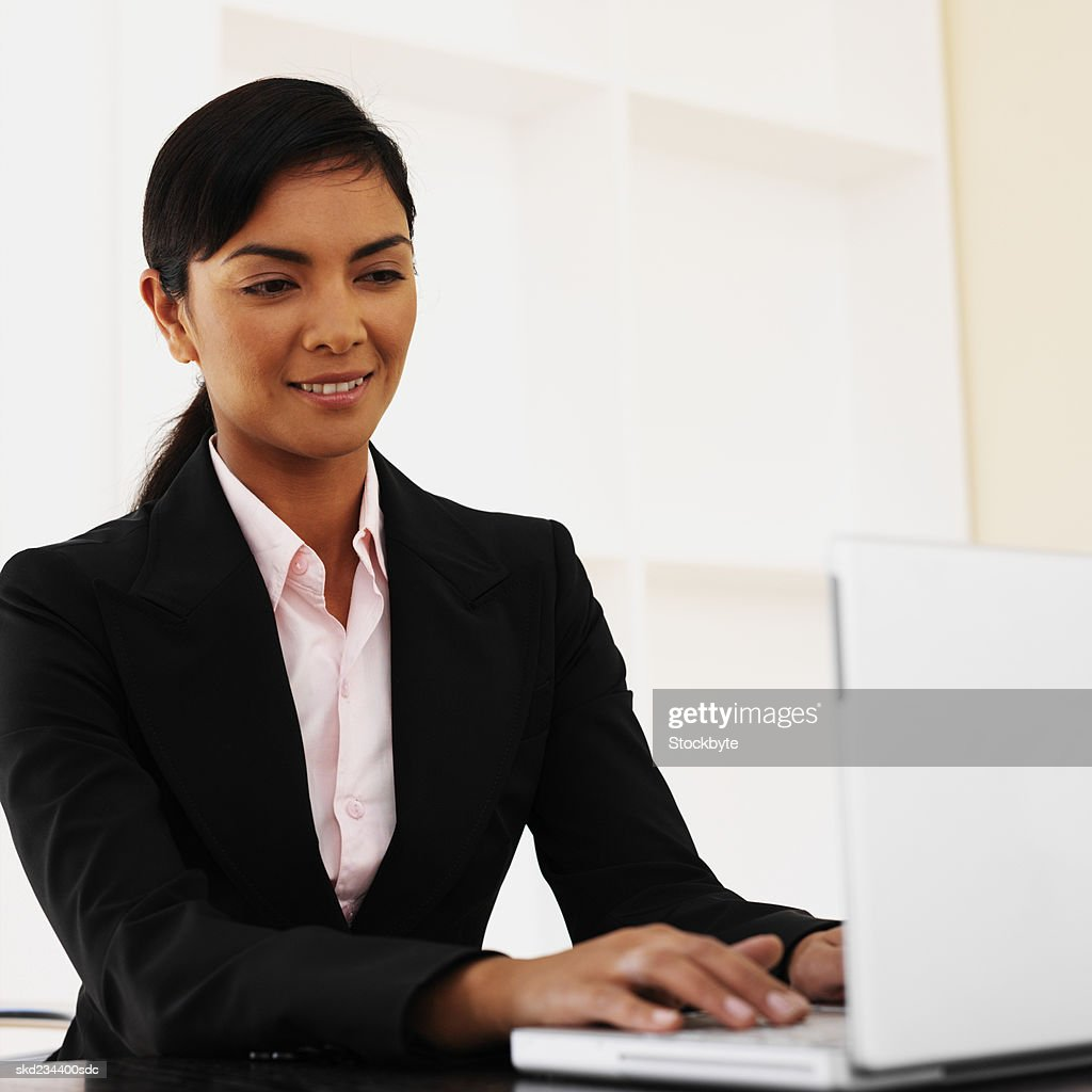 Side view of a businesswoman using a mobile phone : Stock Photo
