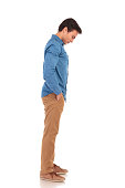 side view of a casual young man looking down to something standing with hands in pockets