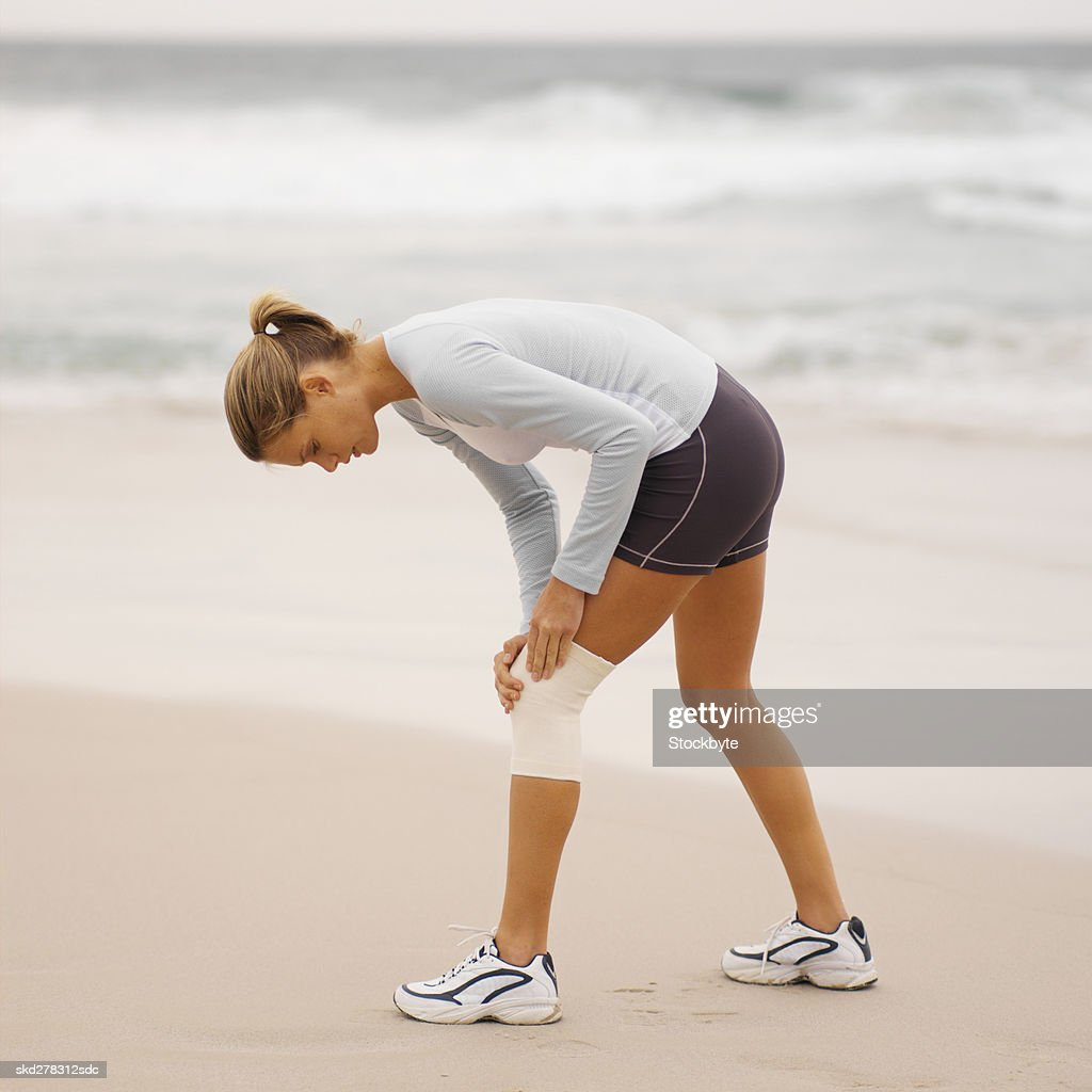 Side view of a concerned woman wearing a knee support holding her knee