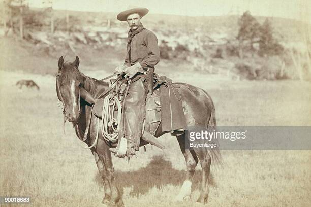 side view of a cowboy on a horse looking towards the camera