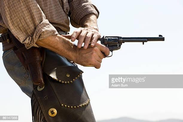 Side view of a cowboy shooting a gun