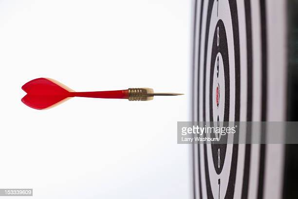 Side view of a dart flying towards the bull's eye of a target