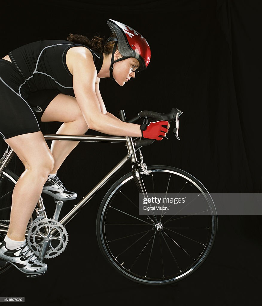 Side View of a Female Cyclist Riding a Bike : Stock Photo