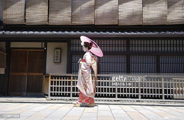 Side view of a Geisha woman walking on a street