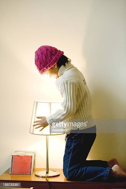 Side view of a girl looking into a lampshade