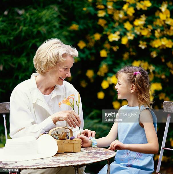 Side View of a Grandmother Sitting With Her Granddaughter at a Garden Table