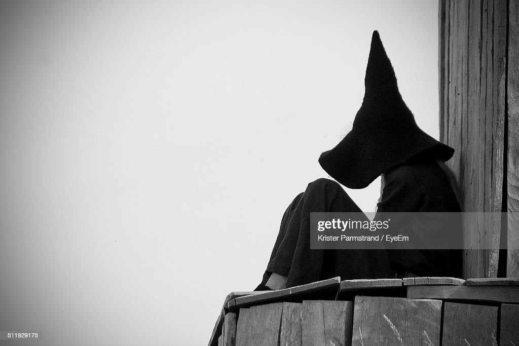 Side view of a Halloween witch sitting against clear sky