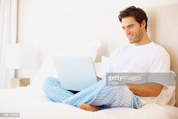 Side view of a happy man working on laptop
