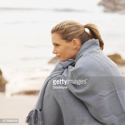 Side view of a happy woman sitting at the beach with a blanket around her