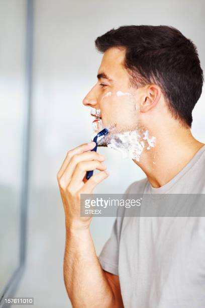 Side view of a male looking at mirror and shaving