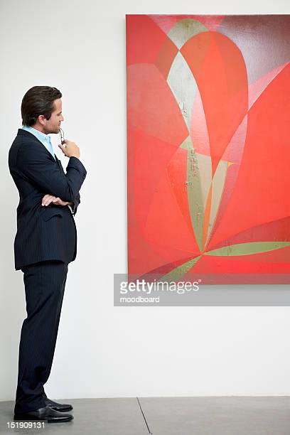 Side view of a man looking intensely towards painting