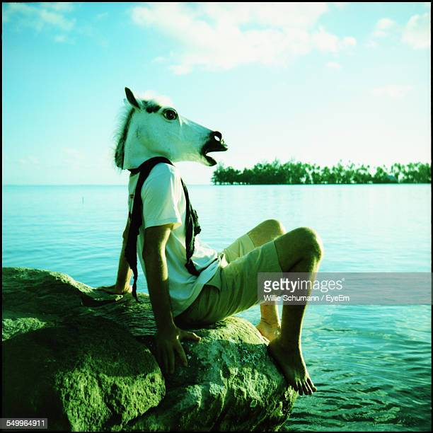Side View Of A Man With Animal Head Overlooking Calm Sea