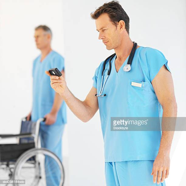 Side view of a mature surgeon looking at pager with colleague pushing wheelchair in background