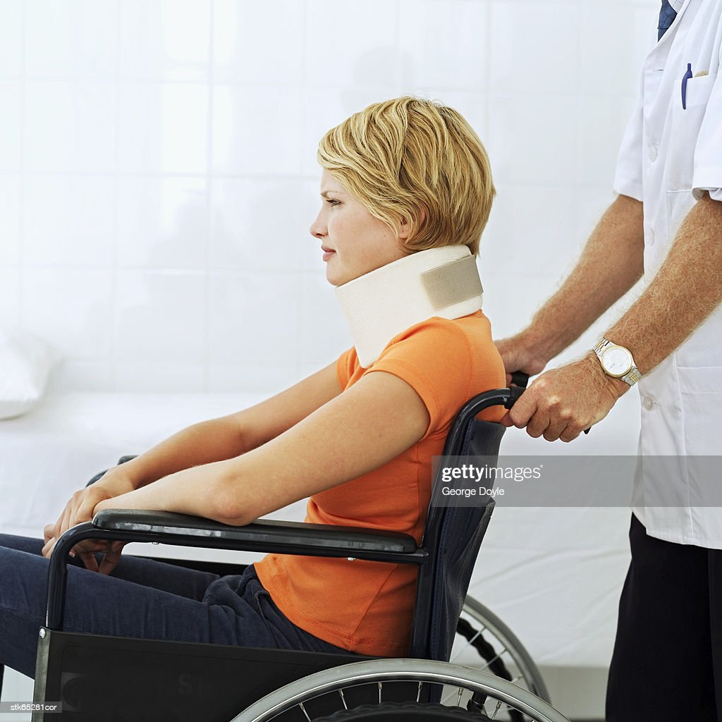 Side View Of A Person Pushing A Woman In A Wheelchair