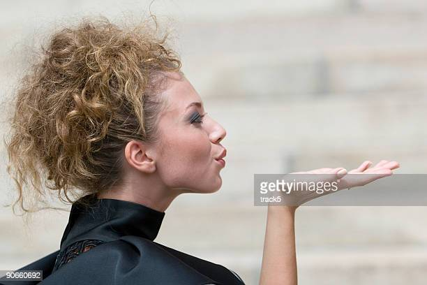 Side view of a pretty female model blowing a kiss