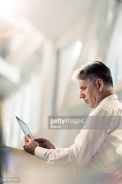 Vue latérale d'un homme d'affaires senior à l'aide de tablette numérique.