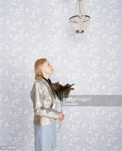 Side View of a Senior Woman Holding a Feather Duster Standing Below a Chandelier