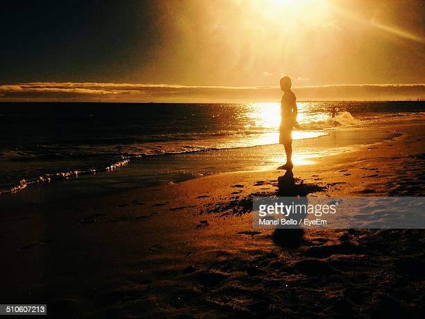 Side view of a silhouette boy on beach at sunset