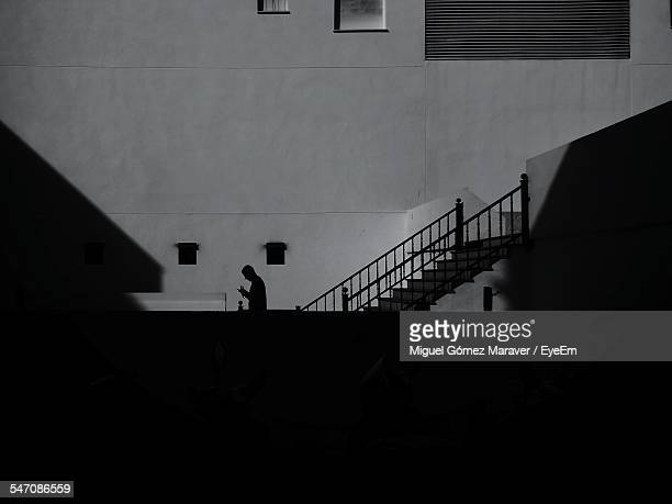 Side View Of A Silhouette Man Walking Against Wall