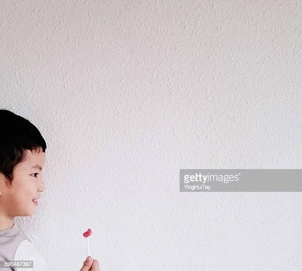 Side view of a smiling boy holding half eaten lollipop