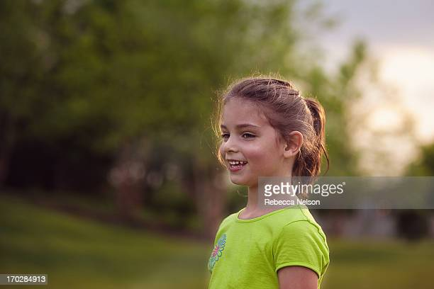 Side view of a smiling girl at sunset