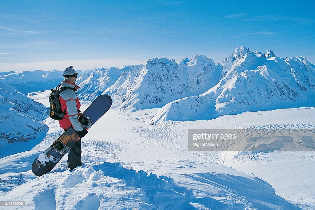 Side View of a Snowboarder Looking at the View of a Snow-covered Mountain Valley : Stock Photo