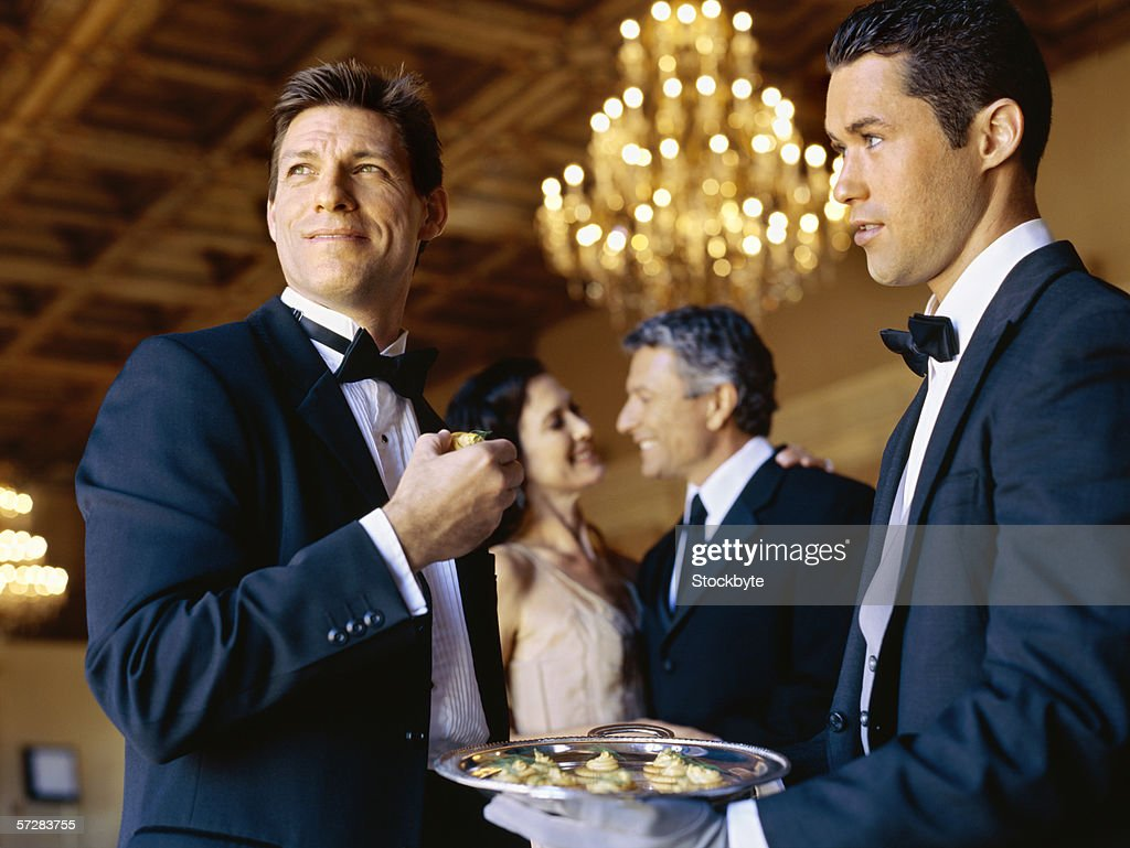 Side view of a waiter serving a mid adult man