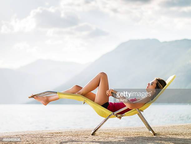 Side view of a woman relaxing in deck chair.