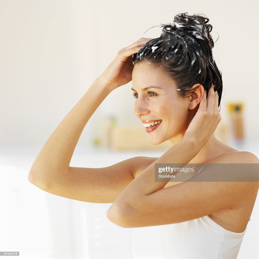 Side view of a woman scrubbing her hair : Stock Photo