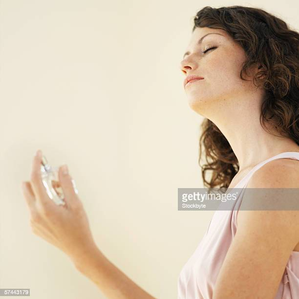 Side view of a woman spraying perfume on herself