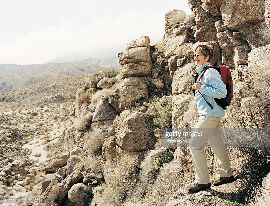 Side View of a Woman Standing Looking at the View of the Desert From a Hill Slope