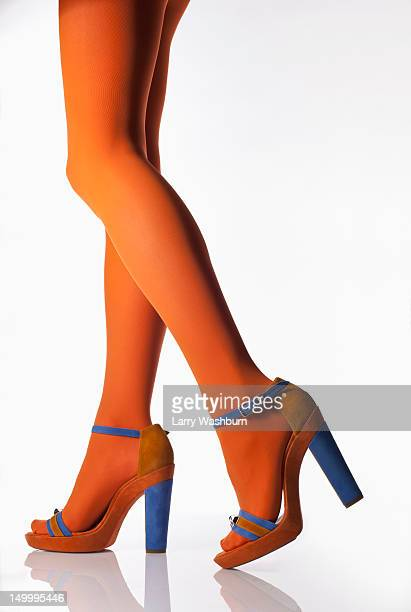 Side view of a woman wearing orange tights and high heels, low section