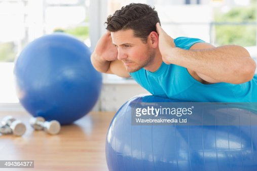 Young man exercising on fitness ball at a bright gym : Foto de stock